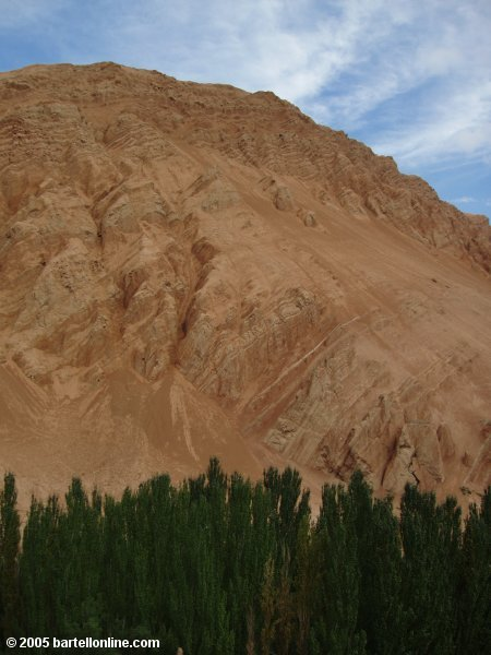 A red-tinted mountain rises above the trees near Bezeklik Grottos in Xinjiang province, China