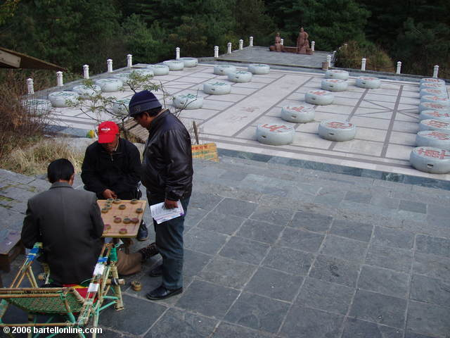 "Men play Chinese chess in front of a much larger board near the end of ""Cloudy Tourist Road"" above Dali, China"
