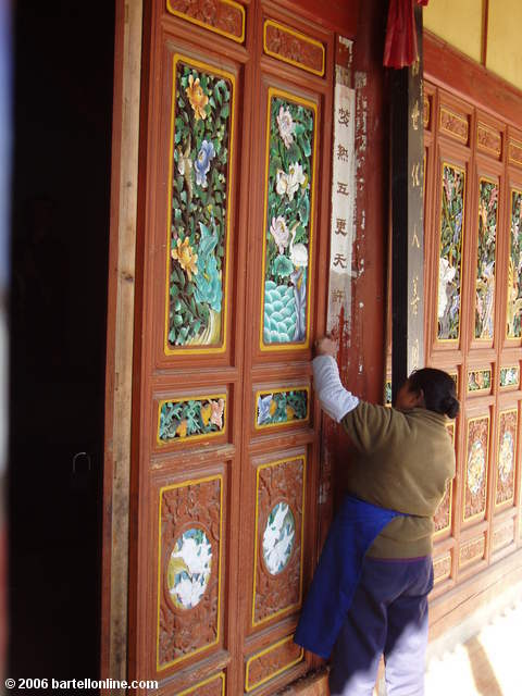 Woman cleans colorful woodwork at the Zhonghe Temple in the Cangshan mountains above Dali, Yunnan, China