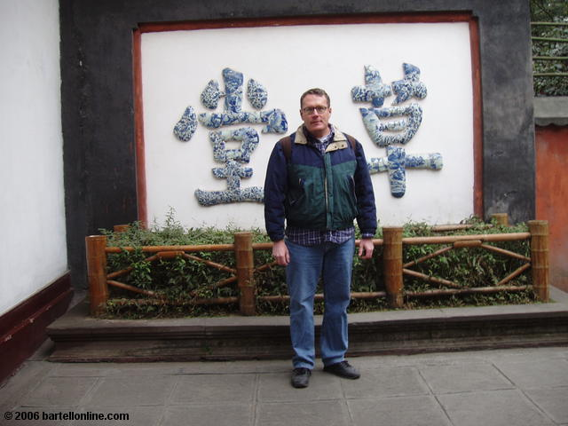 Author poses beside the Stone Wall at Du Fu's Thatched Cottage in Chengdu, Sichuan, China
