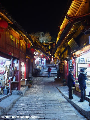 Night view of souvenir shops lining a cobblestone alley in the Old Town of Lijiang, Yunnan, China