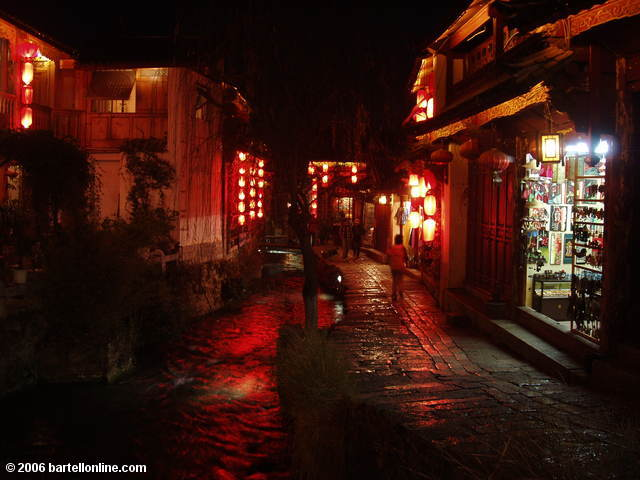 Night view of souvenir shops along a canal in the Old Town of Lijiang, Yunnan, China