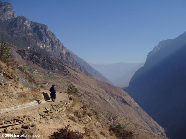 Woman in local minority dress strolls along the upper trail through Tiger Leaping Gorge in Yunnan, China