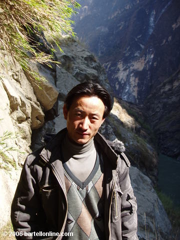 Local toll collector along a narrow cliffside trail through Tiger Leaping Gorge in Yunnan, China