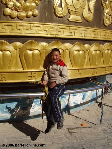 "Small boy rides the giant Buddhist prayer wheel in Zhongdian (""Shangri-La""), Yunnan, China"
