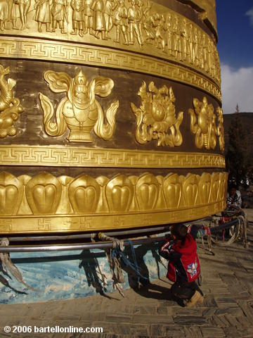 "Small boy struggles to turn the giant Buddhist prayer wheel in Zhongdian (""Shangri-La""), Yunnan, China"