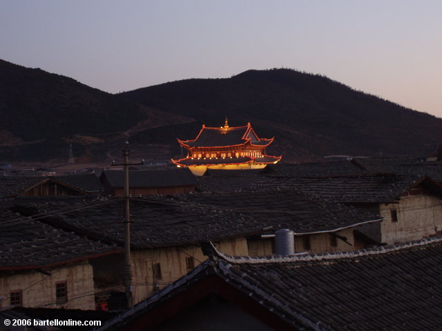 "Lighted Buddhist temple seen above roofs in the old town section of Zhongdian (""Shangri-La""), Yunnan, China"